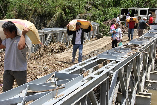 Personnel of the SWAD- Mountain Province,provincial government,  Sabangan Bauko,and Tadian MDRRMCs haul and carry the relief goods across the Sabangan Detour Bridge.